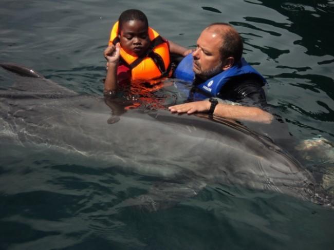 Jayden schwimmt mit dem Delfin