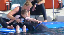 Barbara bir yunus ile oynayan bir çocuk yardım