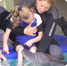 barbara with child during the therapy in open seawater dolphinarium